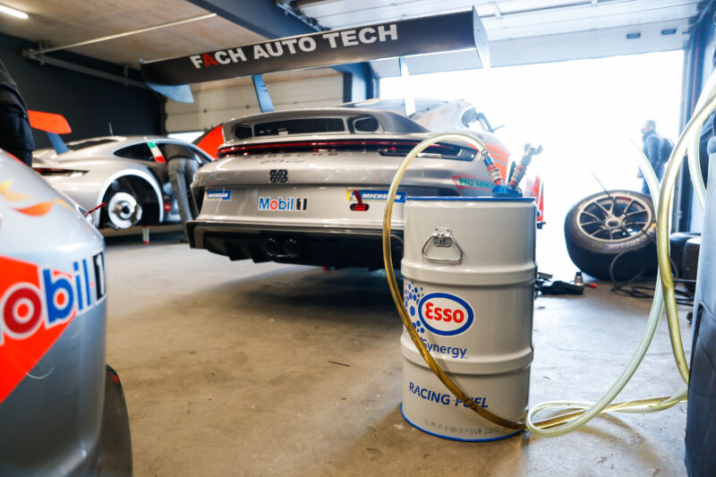 A barrel of fuel in front of a Porsche racing car in its garage.