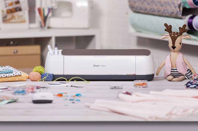 A Cricut maker in its natural habitat: a carefully staged table full of miscellaneous crafting bits.