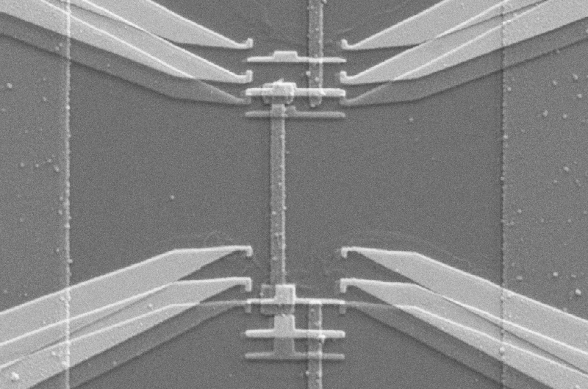 Scanning electron micrograph shows the device used to implement the gambling demon. The tapered structures on each side are electrodes from which single electrons can jump onto the strip-shaped copper island in between. Each jump is like a gas molecule passing through the demon's shutter.