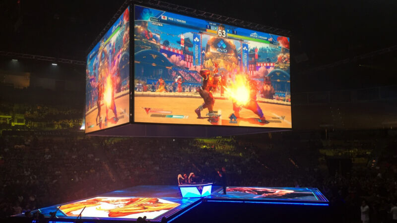 A video game plays on giant screens over a packed arena.