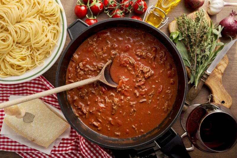 Bolognese sauce in a pan, next to a bowl of spaghetti.