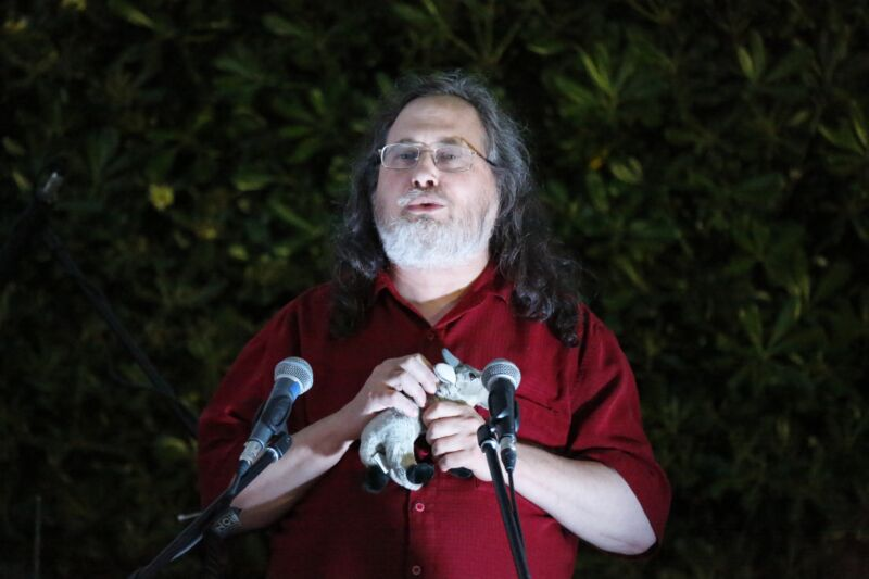 Richard Stallman speaking in front of microphones while holding a stuffed animal.