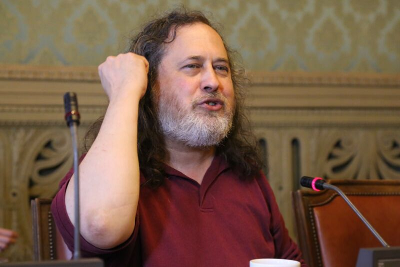 Richard Stallman speaking to an audience while seated at a table.