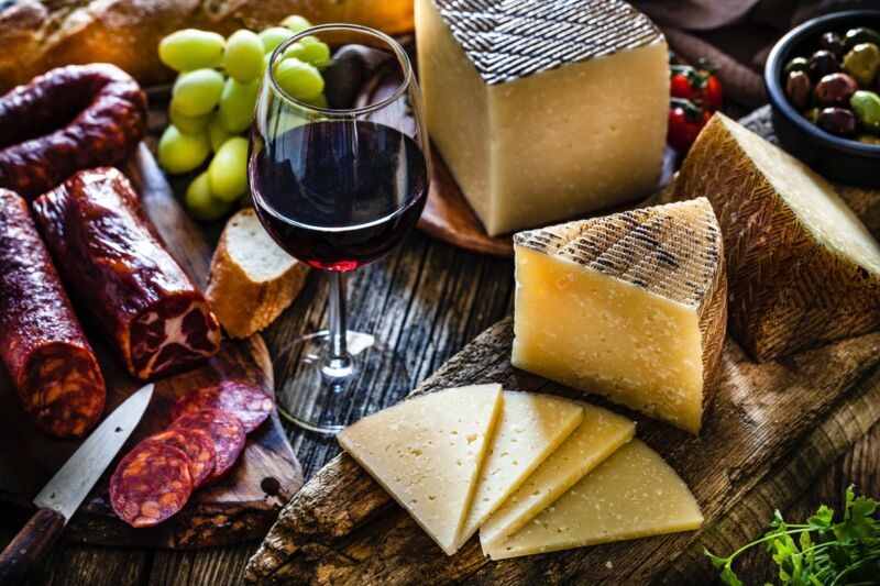 Manchego cheese slices and pieces in a cutting board shot on dark rustic wooden table, with glass of red wine.