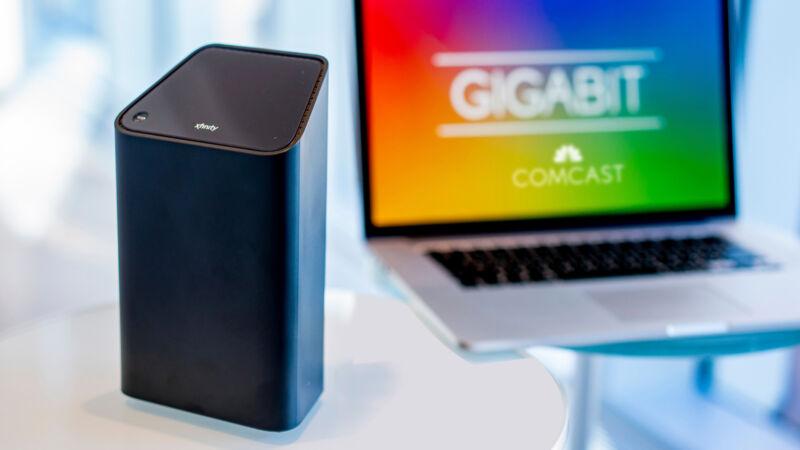 A Comcast modem/router gateway sitting next to a laptop.