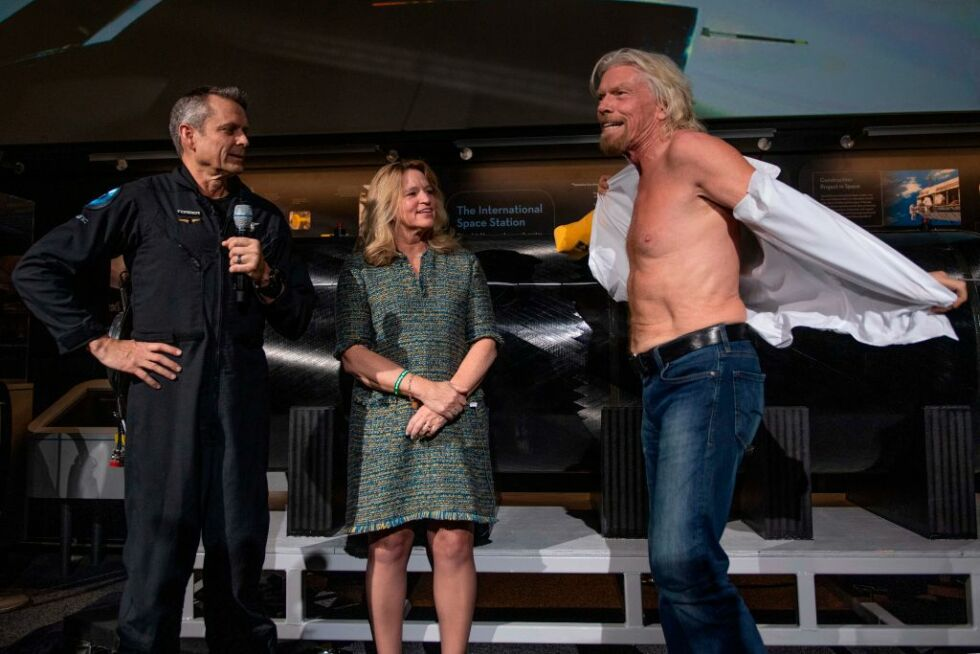 "Sir Richard Branson takes off his shirt to don a T-shirt that says ""Future Astronaut Training Program."" The shirt was given to him by Virgin Galactic Test Pilot Mark ""Forger"" Stucky as Air and Space Museum Director Ellen Stofan looks on."