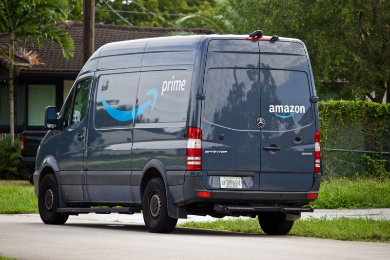 A dark blue van with multiple Amazon logos.