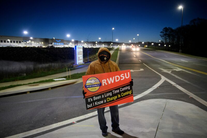 A union supporter stands before sunrise outside the Amazon fulfillment center on March 29, 2021 in Bessemer, Alabama.