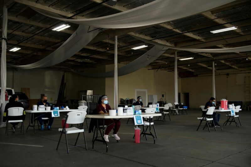 Nurses wait at empty tables for more patients to arrive to receive a dose of the Moderna Covid-19 vaccine at a pop-up vaccination site in Gardena, California, on April 17, 2021.
