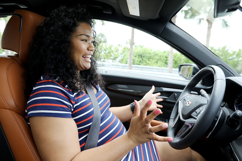 A surprised woman gleefully lets go of her car's steering wheel.
