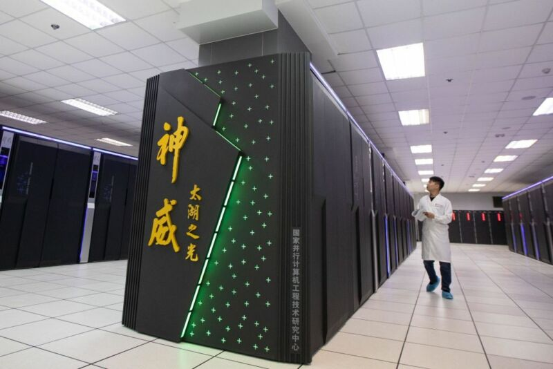 A staff member works beside China's 'Sunway TaihuLight' supercomputer at the National Supercomputer Center on August 29, 2020 in Wuxi, Jiangsu Province of China.