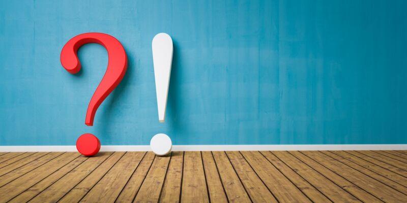 تصویر علامت سوال و علامت تعجب در کف چوبی که به دیوار تکیه داده است.