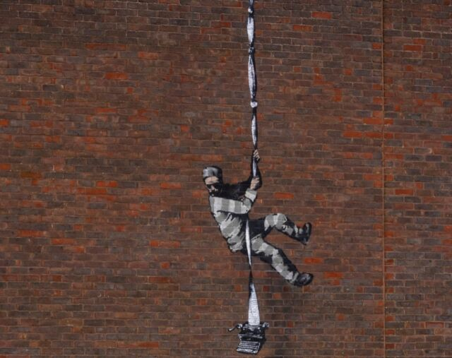Art work by graffiti artist Banksy, depicting a prisoner escaping with a typewriter—a tribute to one of its famous former prisoners, Oscar Wilde—in Reading, England.