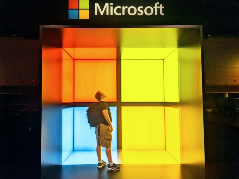 A randomly dressed man stands inside a giant Microsoft logo.