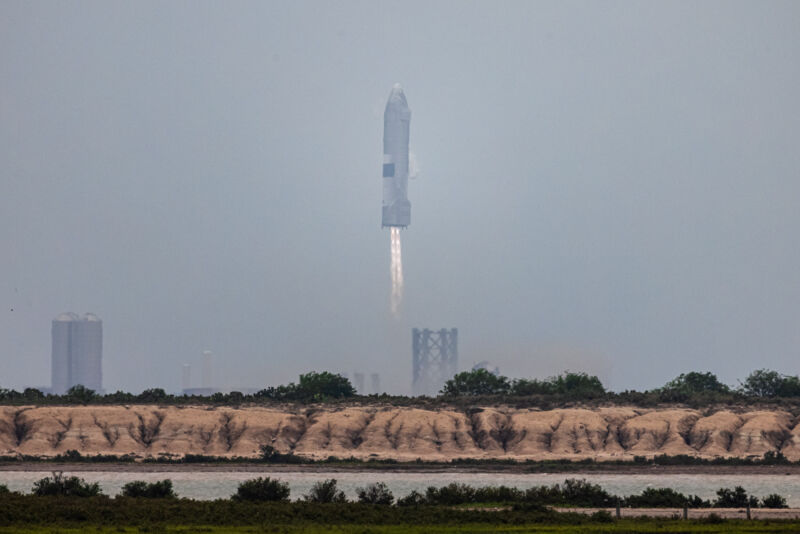 Image of a rocket with engines firing just above its landing pad.