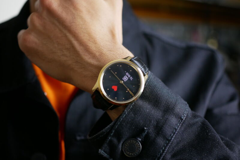 he Garmin vivomove luxe on a user's wrist with the screen on, showing heart rate next to the watch hands.