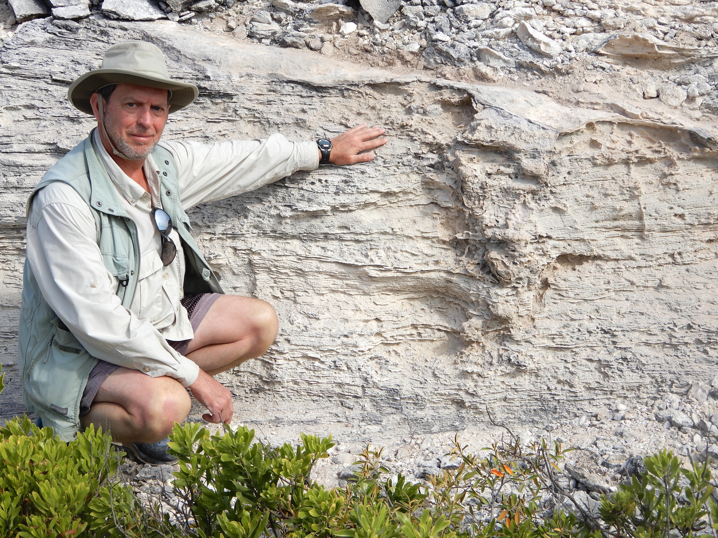 Anthony Martin shows off a section of rock that contains a trace fossil of an iguana burrow.