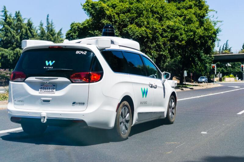 A Waymo-branded minivan prowls suburban streets.