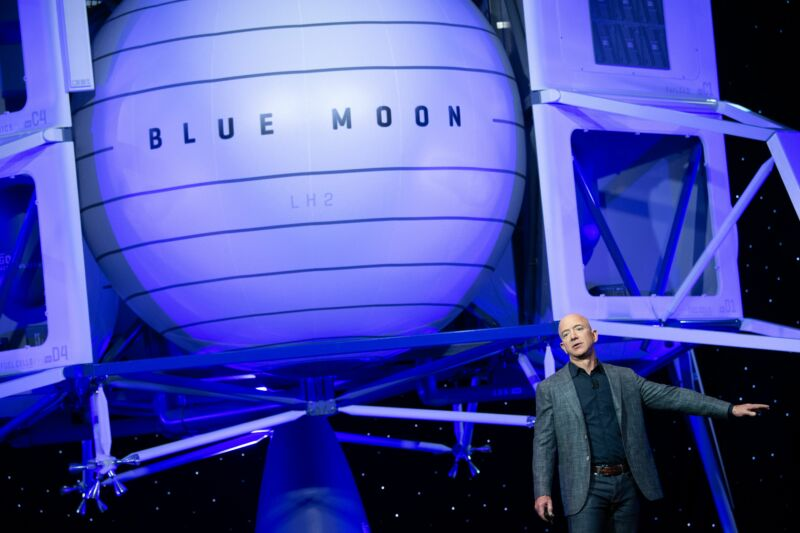A man in a sport coat speaks next to a life-sized image of a small spacecraft.