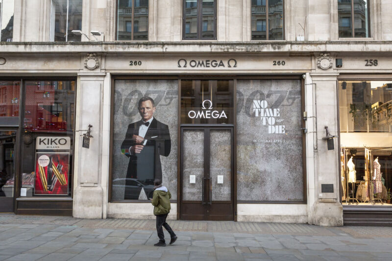A man walks past a promotion for the James Bond fIlm <em>No Time to Die</em> at the closed Omega store in London on March 27, 2020.
