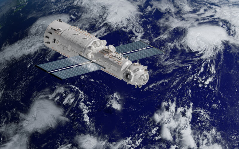 Image of a space craft with solar panels with the earth in the background.