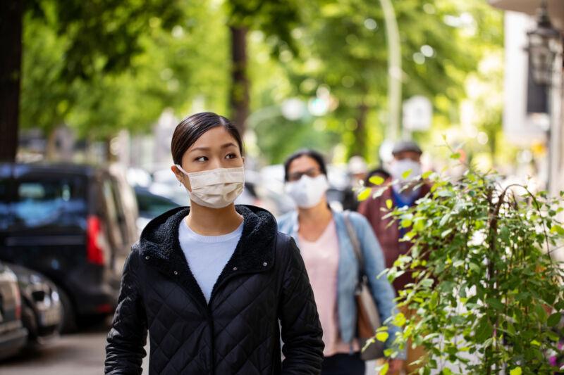 A masked woman walks along a treelined city street.