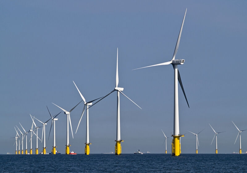 Image of a row of wind turbines in the ocean.