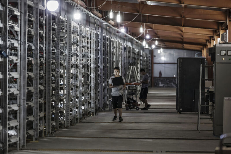 Technicians inspect bitcoin mining machines at a mining facility operated by Bitmain Technologies Ltd. in Ordos, Inner Mongolia, China, on Friday, Aug. 11, 2017.