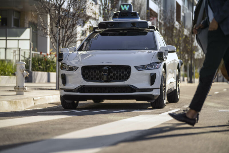 One of Waymo's sensor-studded Jaguar I-Paces observes a pedestrian crossing the road in front of it.