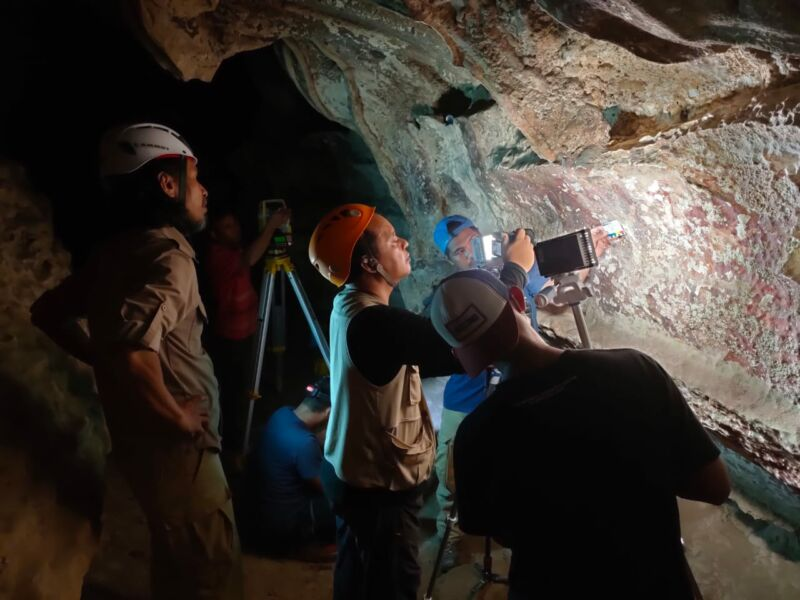 color photo of archaeologists examining rock art in a dark cave