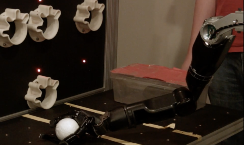 A robotic arm grasps a white spherical object.
