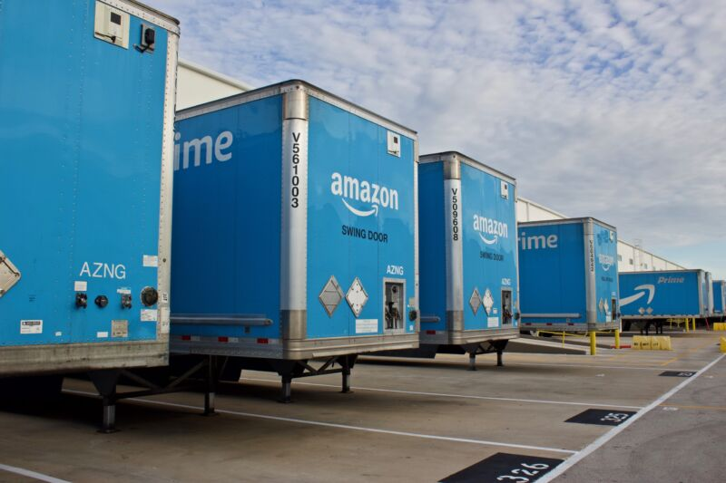 Several Amazon trailers lined up outside a shipping center.