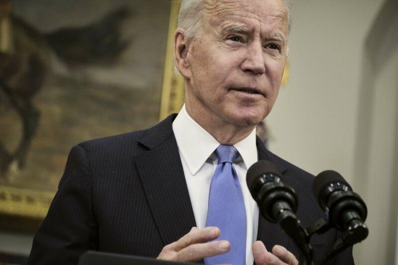 President Joe Biden standing and speaking in front of microphones.