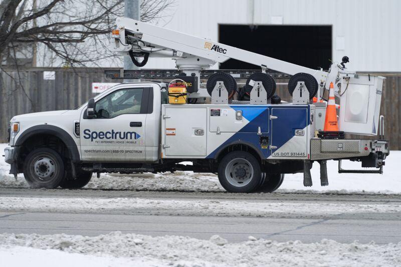 A Charter Spectrum service truck on a snowy street.