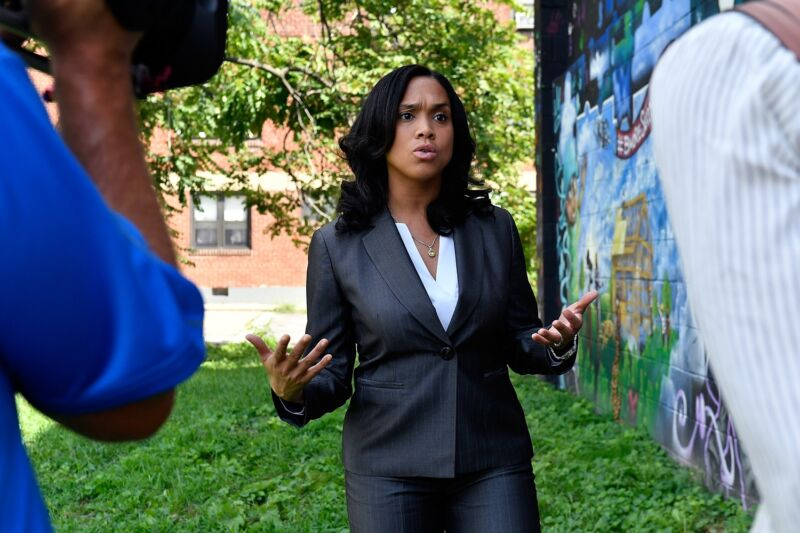 Baltimore chief prosecutor Marilyn Mosby standing outside and talking to a reporter as a person holding a camera films.