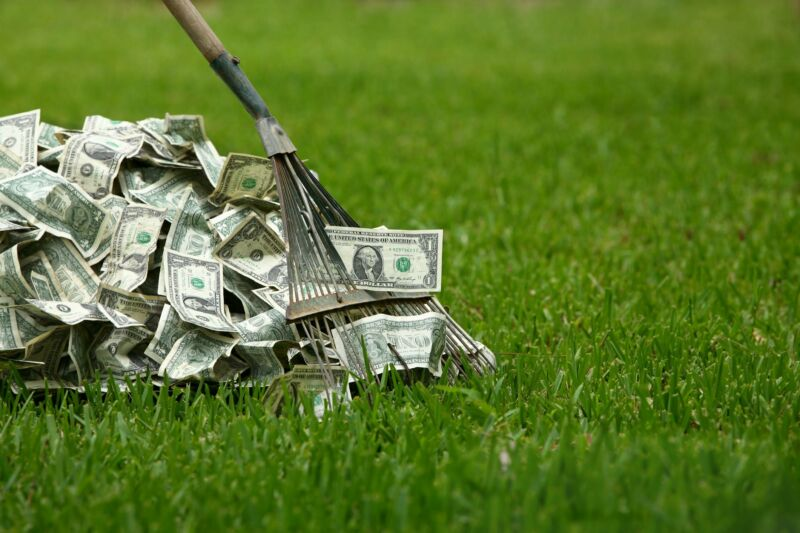 A rake being used to gather a pile of money on a lawn.