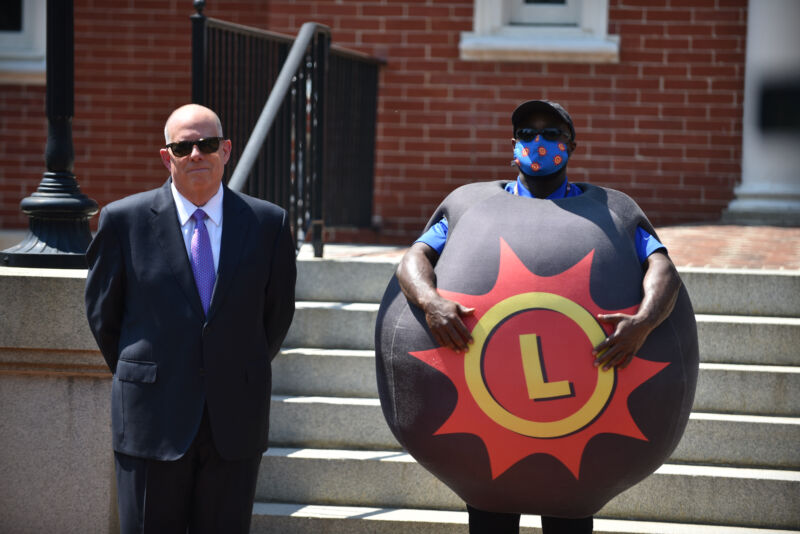 Maryland Governor Larry Hogan stands next to a person dressed as a lottery ball during a press conference on May 20 announcing the state's VaxCash promotion.