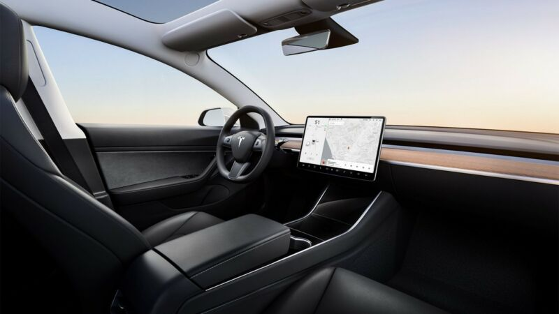 Interior of a Tesla Model 3, with a mounted device showing an area map and directions.