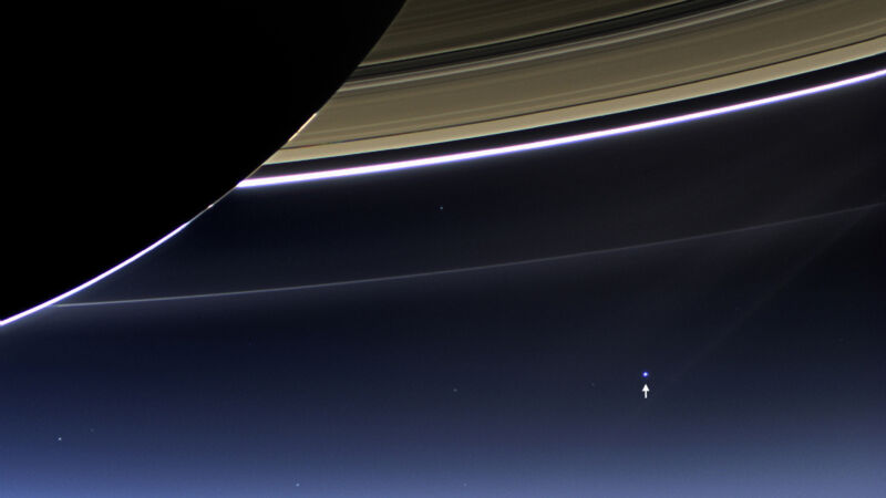Image of the Earth as a small dot below Saturn's rings.