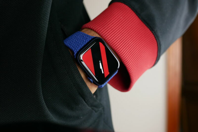 Extreme close-up photograph of a wristwatch on a hand in a pants pocket.