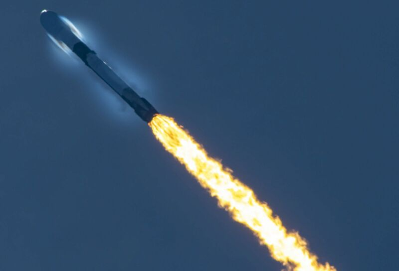 A launching rocket leaves a trail of flame against a dark blue sky.