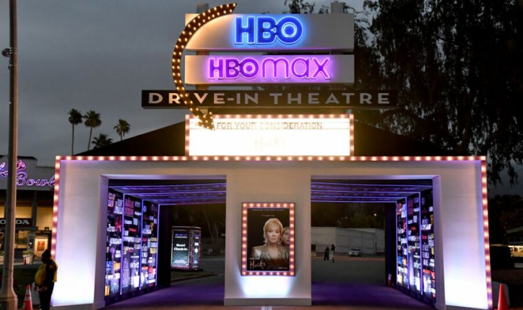 The entrance to a drive-in theater has been manipulated to include promotional posters for current HBO offerings.