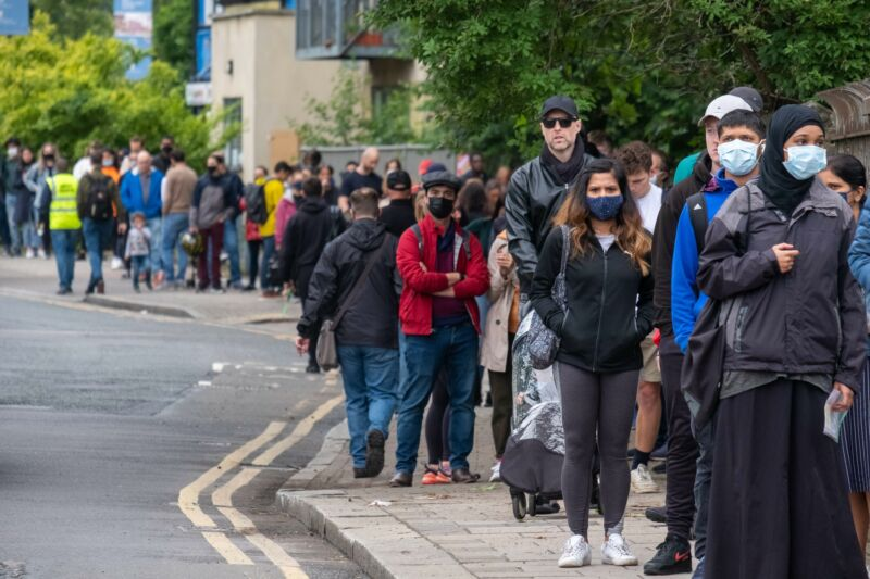 People line up outside Bridge Park Community Leisure Center to receive the COVID-19 vaccines in Brent, northwest London, June 19, 2021. A new wave of coronavirus infections is