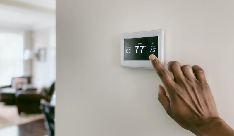 Close-up of woman's hand adjusting air conditioning setting on thermostat.