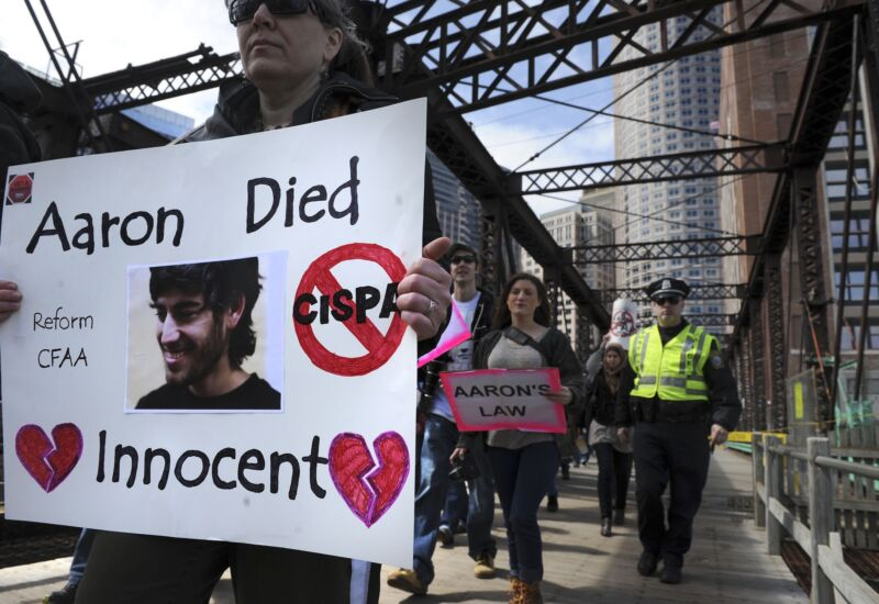 Protesters walking across a bridge. One holds a sign with a picture of Aaron Swartz that says,
