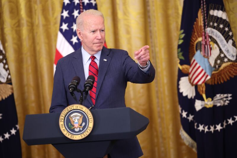 President Joe Biden standing at a dais and pointing as he speaks at a press conference.