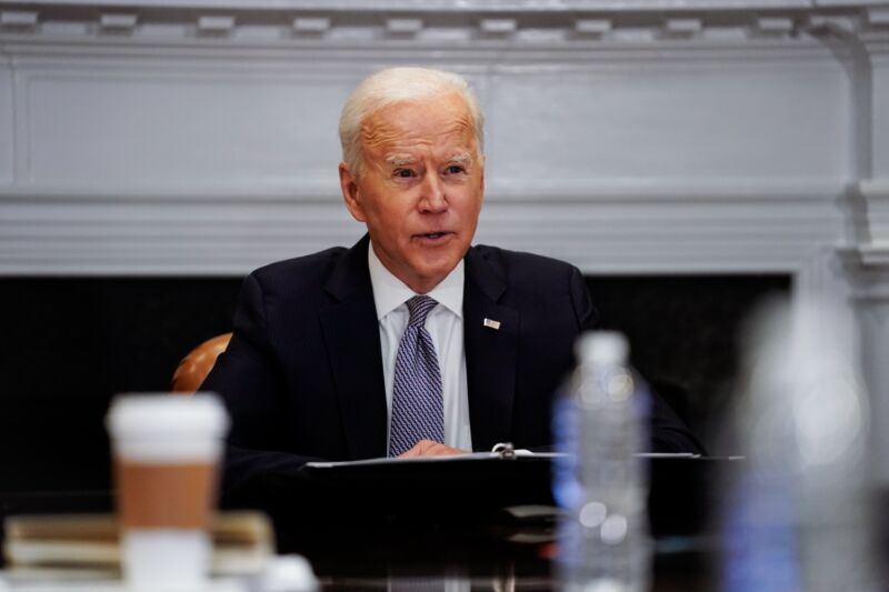 President Biden sitting at a table and speaking while gesturing with his hand.