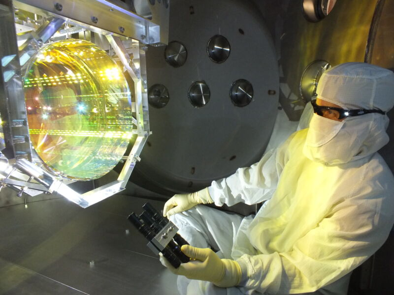 A researcher in protective gear examines an impossibly futuristic mirror.