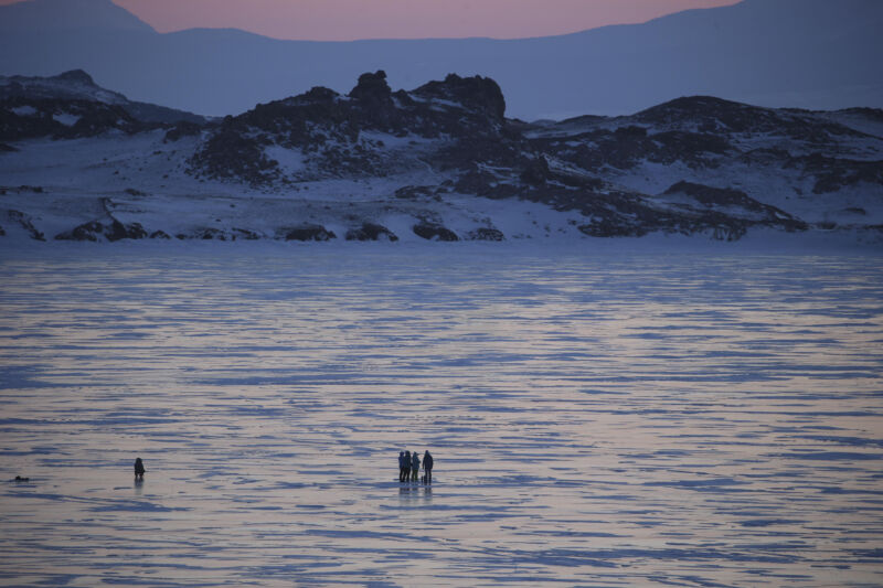 Tiny figures walk on a frozen lake at sunset or sunrise.