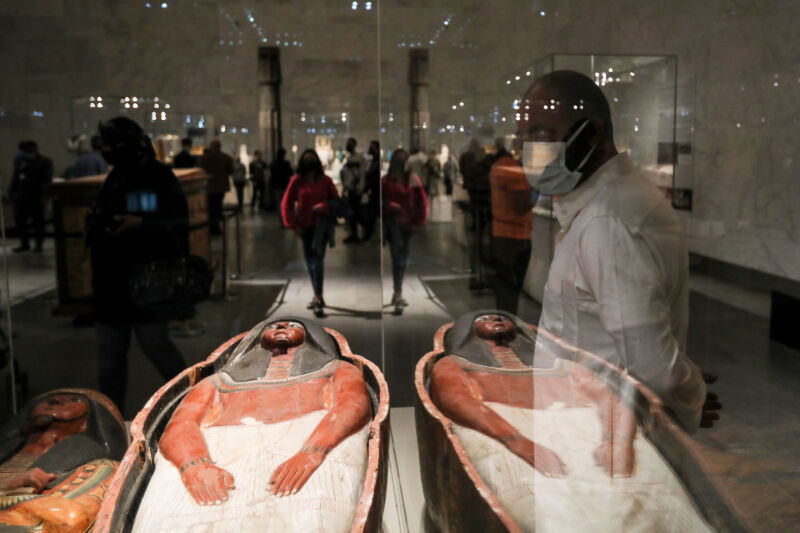 A visitor looks at displayed artifacts at the National Museum of Egyptian Civilisation (NMEC) during its official reopening a day after the Pharaohs' Golden Parade ceremony, a procession held to transport the mummified bodies of 22 ancient Egyptian kings and queens from the Egyptian Museum to their new resting place at the NMEC.